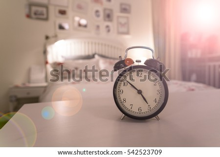 Retro Alarm Clock On Bedside Table At Morning Day. Alarm Clock In The Sweet  Bedroom