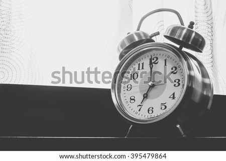 Retro alarm clock on head of a bed with sunlight black and white color