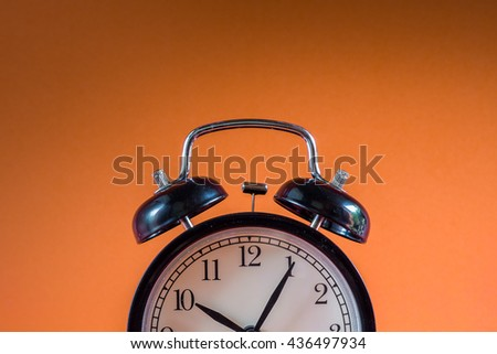 Retro alarm clock on orange background,Clock concept background,clock with copy-space,ten o'clock and five minute - stock photo