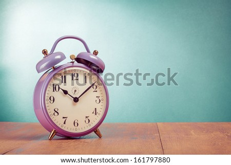 Retro alarm clock on table front mint green background - stock photo