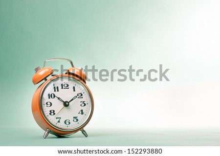 Retro alarm clock on table on mint green background - stock photo