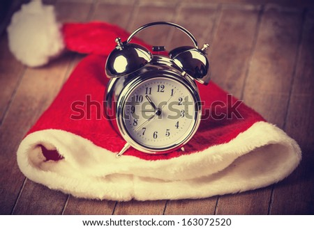 Retro alarm clock on table with christmas hat - stock photo