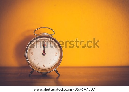 Retro alarm clock on table with yellow wall background,vintage color tone