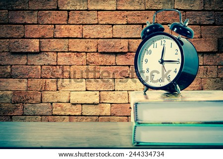 Retro alarm clock on text book with brick wall background  - stock photo