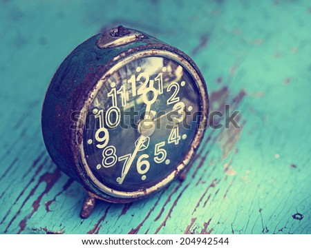 Retro alarm clock on wooden rusty background - stock photo