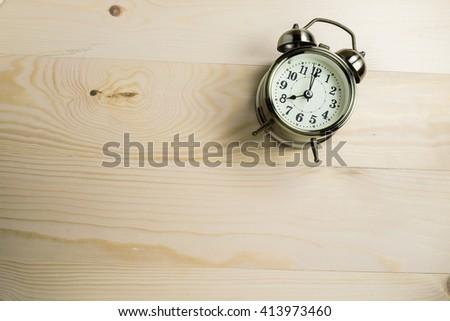 Retro alarm clock on wooden table. time concept - stock photo