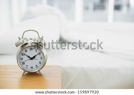 Retro Alarm Clock Standing On A Bedside Table In A Bedroom