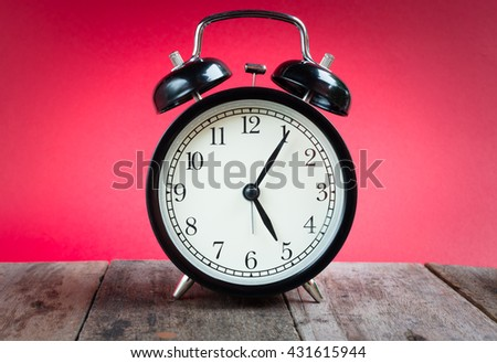 Retro alarm clock with five o'clock and five minute on red background. Clock concept. - stock photo