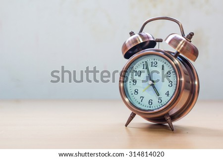 Retro alarm clock with old wall on table