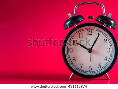 Retro alarm clock with Ten o'clock and five minute on red background.Clock concept.  - stock photo