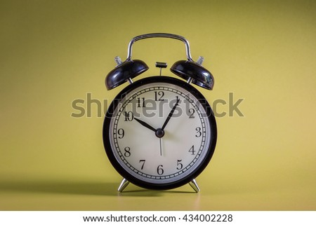 Retro alarm clock with Ten o'clock and five minute on soft yellow background - stock photo