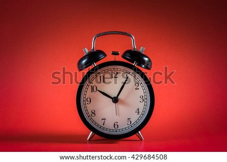 Retro alarm clock with ten o'clock and five minutes with red background vintage style tone.  - stock photo