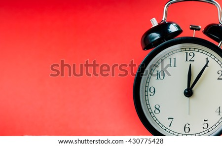 Retro alarm clock with Twelve o'clock and five minutes. Vintage style colour. - stock photo