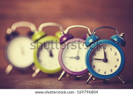 Retro alarm clocks on a table. Photo in retro color image style - stock photo