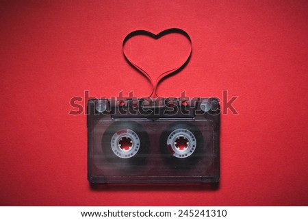 Retro audio cassette with magnetic tape in shape of heart on red background. Valentines day card