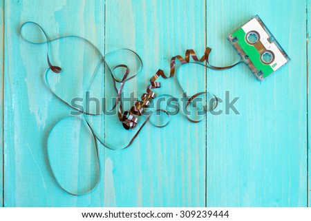Retro audio cassette with pulled out tape on the blue  background - stock photo