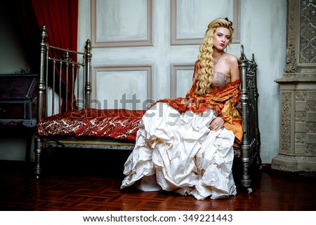 Retro baroque fashion blonde woman wearing gold dress.