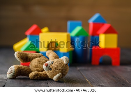 Retro Bear toy alone on wooden floor with bilding blocks - stock photo