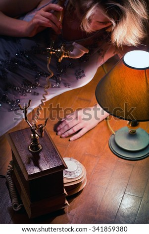 retro beautiful girl with a vintage telephone in the dim light from a floor lamp in the style of the twenties the jazz era - stock photo