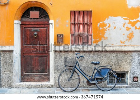 Retro bicycle standing near the old door, Italy. - stock photo