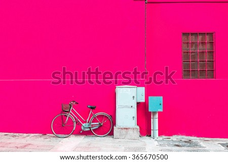 Retro bicycle standing over empty pink wall. - stock photo