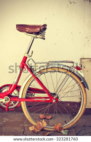 Retro bicycle with autumn leaves on the rear wheel. Vintage style. Vertical image
