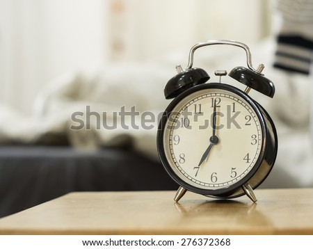 Retro black alarm clock show 7 o'clock in the morning for wake up.Background is a bedroom. - stock photo