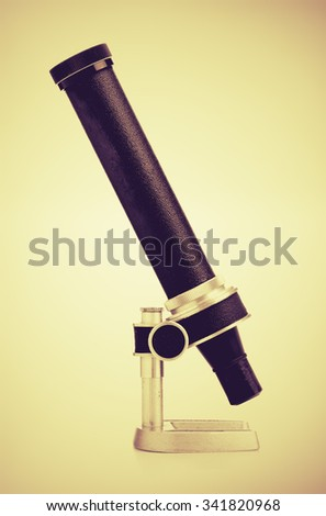 Retro black and metal microscope side view vintage filtered - stock photo