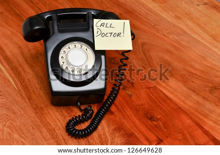 Retro black telephone with reminder note to call the doctor - stock photo