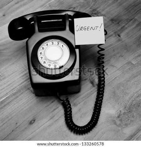 Retro black telephone with urgent reminder note - stock photo