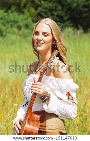 Retro blonde 70s hippie girl with acoustic guitar outdoor in nature. Standing in meadow.