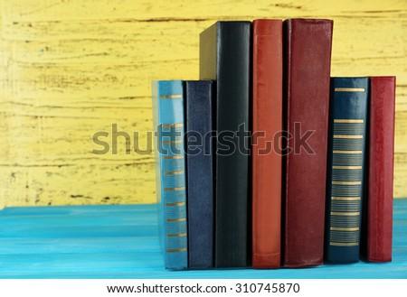 Retro books on yellow wooden background - stock photo