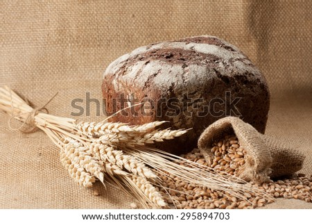 retro bread in rustic style background.Fresh traditional bread on wooden ground with flour in a sack. wheat germs and flour.