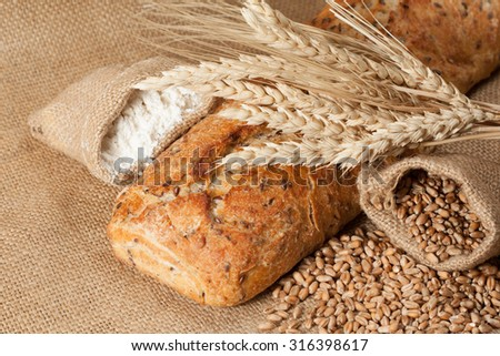retro bread in rustic style background.Fresh traditional bread on wooden ground with flour in a sack.