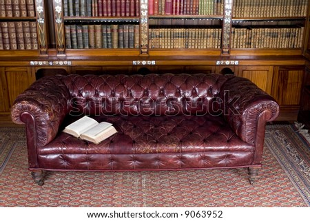 Retro brown leather couch with open book - stock photo