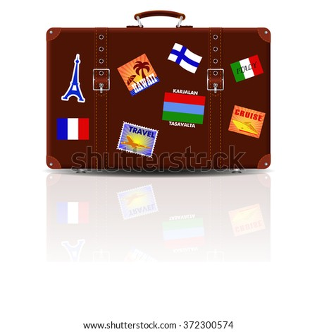 Retro brown leather suitcase with stickers from his travels. - stock photo
