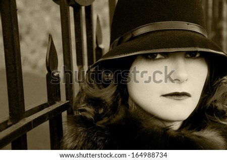 Retro brunette in the hat in the autumn light - stock photo