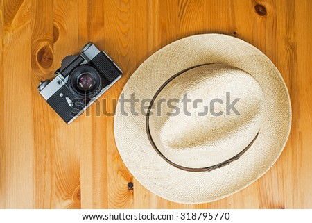 Retro camera and a hat on wooden background, travel concept - stock photo