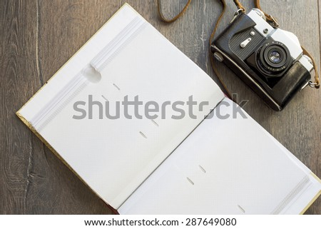 retro camera and a photo album on a wooden background - stock photo