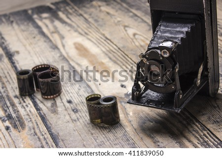 Retro camera and film on wooden background