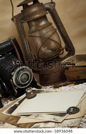 Retro camera, kerosene lamp and old photos - stock photo