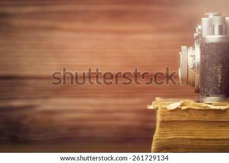 Retro camera on old book over wooden defocused background. Vintage filtered effect. Shallow DOF - stock photo