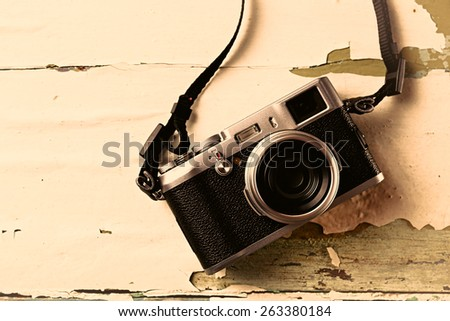 Retro camera on old color wooden table background - stock photo