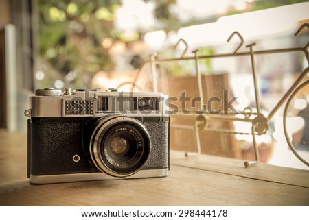 Retro camera on wooden table - stock photo