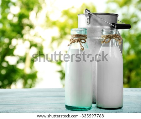 Retro can for milk and glass bottles of milk on nature background