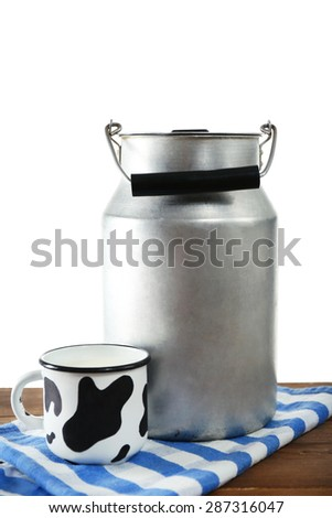 Retro can for milk and mug of milk on wooden table, on white background