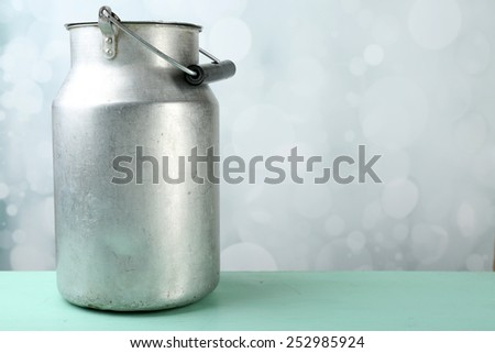 Retro can for milk on wooden table on light background - stock photo