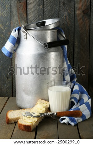 Retro can for milk with fresh bread and glass of milk on wooden background. Bio products concept - stock photo
