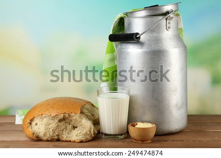 Retro can for milk with fresh bread and glass of milk on wooden table, on bright background. Bio products concept - stock photo