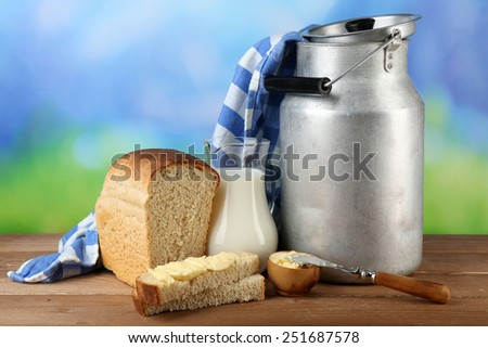 Retro can for milk with fresh bread and jug of milk on wooden table, on bright background. Bio products concept - stock photo